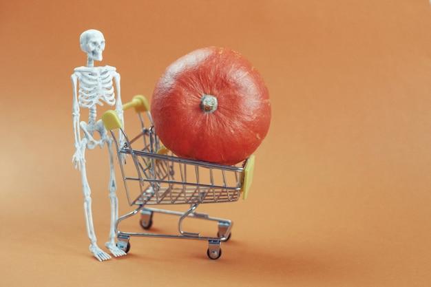 Halloweenowy szkielet z dynią w wózku na pomarańczowym tle