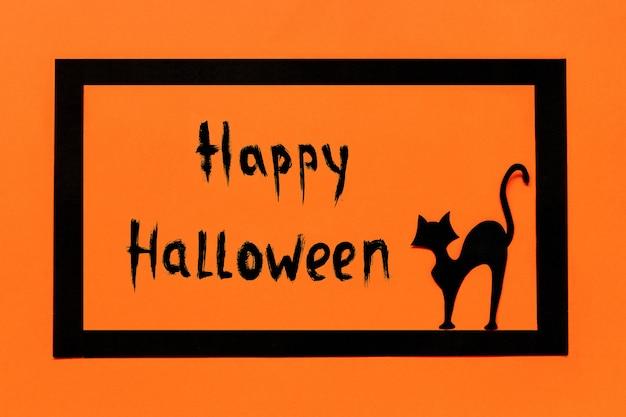 Halloweenowy tło czarny papierowy tekst kota happy halloween w czarnej ramce na pomarańczowym tle.