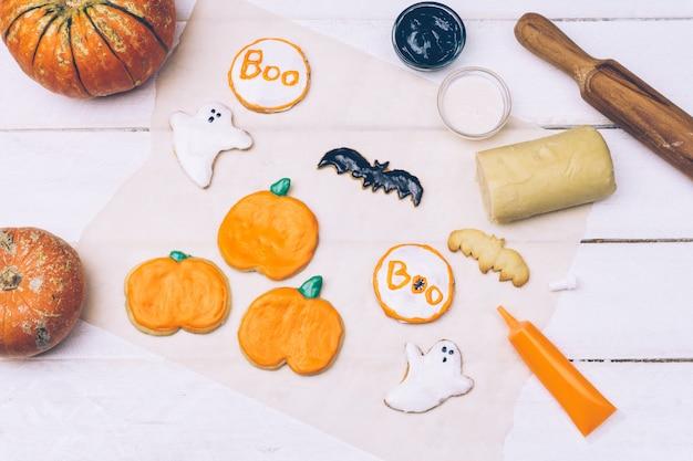 Halloweenowy tło z domowej roboty halloweenowymi ciastkami i baniami na drewnianym stole.