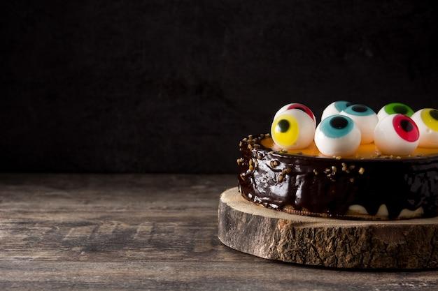 Halloweenowy tort z cukierkiem przygląda się dekorację na drewnianym stole. skopiuj miejsce