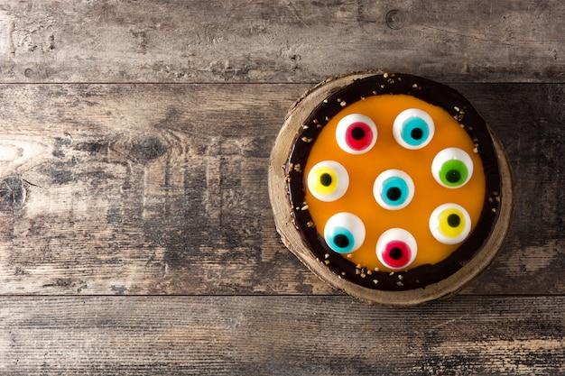 Halloweenowy tort z cukierkiem przygląda się dekorację na drewnianym stole. widok z góry. skopiuj miejsce