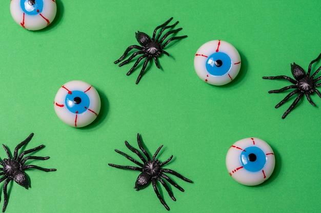 Halloweenowy układ z pająkami i gałkami ocznymi na zielonym tle