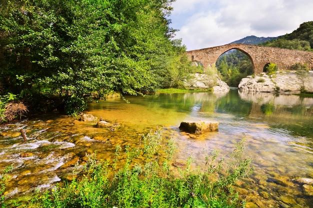 Halna rzeka z średniowiecznym łukowatym mostem w pyrenees