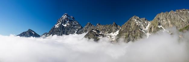Halne szczyty alp nad chmurami przeciw jasnemu niebieskiemu niebu. piemont włochy
