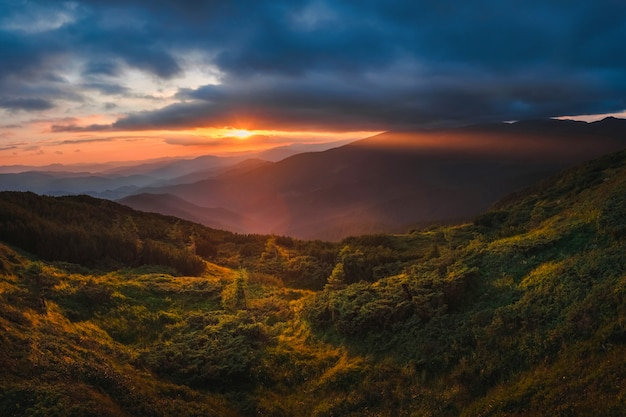 Halny wzgórze z burzowym niebem i sunbeam przy zmierzchem