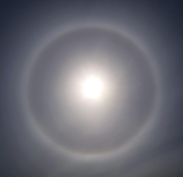 Halo i słońce na niebie chmury i cienka warstwa chmur cirrus.