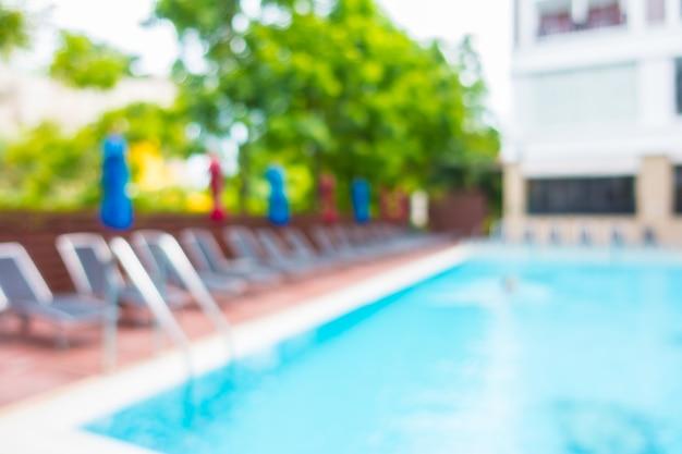 Hamaki z kolorowymi parasolami na basenie rozmytą