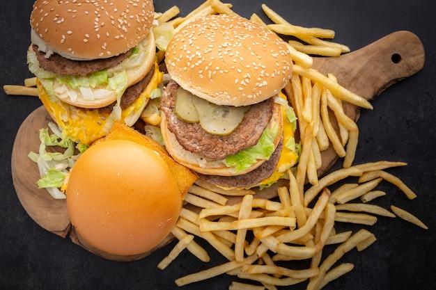 Hamburger, cheeseburger z podwójnym kotletem i frytkami i starą drewnianą deską do krojenia na ciemnym tle tekstury, widok z góry