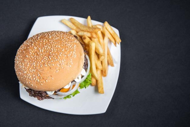 Hamburger i frytki na talerzu na czarnym tle