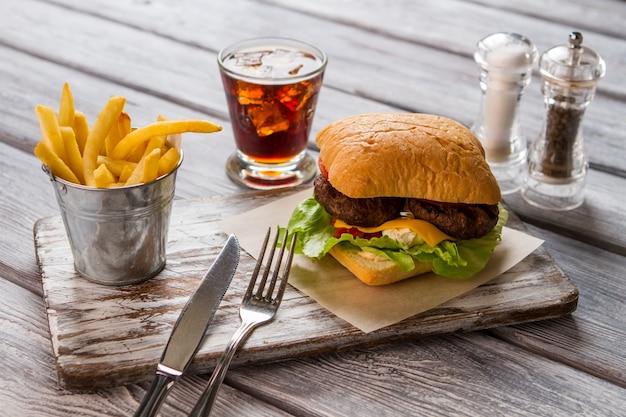 Hamburger i frytki. szklanka coli i przypraw. fast food w amerykańskiej restauracji. soczysta wołowina i ciepły ser.