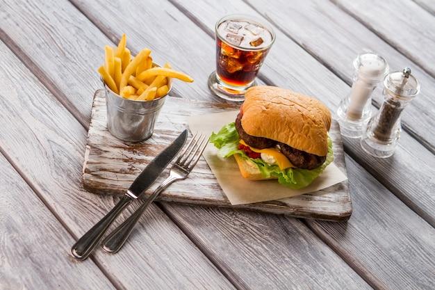 Hamburger i wiadro frytek. szkło z colą. pyszna przekąska w amerykańskiej kawiarni. schłodzony napój o słodkim smaku.