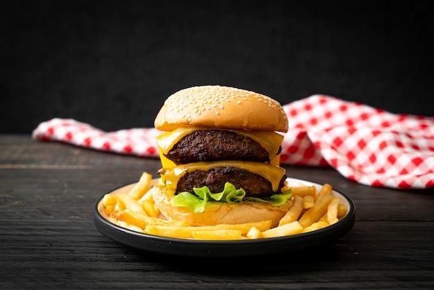 Hamburger lub burgery wołowe z serem i frytkami - niezdrowe jedzenie