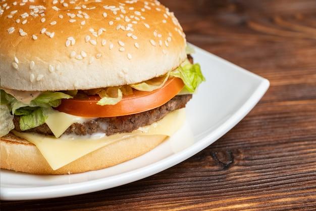 Hamburger na białym talerzu i drewnianym tle z lupą.