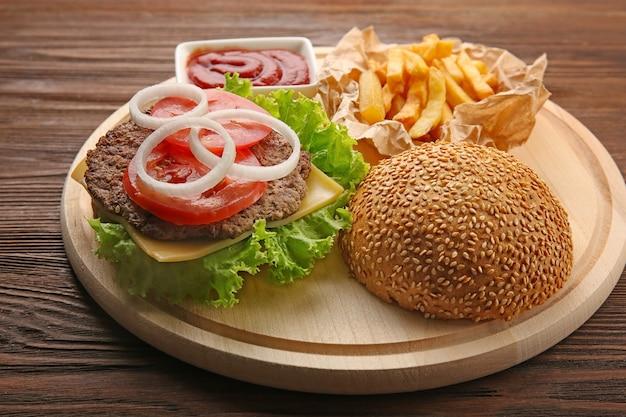 Hamburger na desce do krojenia, zbliżenie