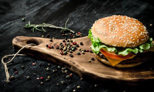 Hamburger na drewnianej desce. na czarnej tablicy.