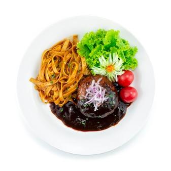 Hamburger steak (hambagu) serwowany makaron japońska dekoracja w stylu fusion z rzeźbionym porem, cebulą i warzywami widok z góry