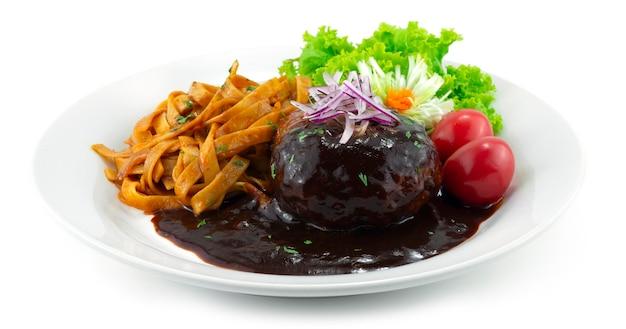 Hamburger steak (hambagu) serwowany makaron japońska dekoracja w stylu fusion z rzeźbionym porem, cebulą i warzywami z boku