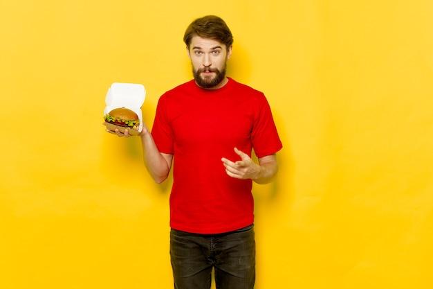 Hamburger w pudełku trzymanym przez młodego mężczyznę