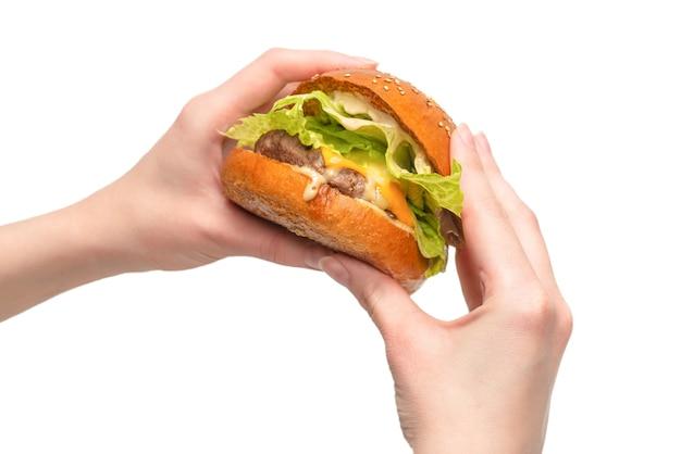 Hamburger w ręce kobiety na białym tle na białej ścianie. widok z góry.