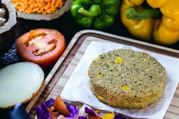 Hamburger wegetariański, zrobiony z soi i zbóż, z warzywami dookoła