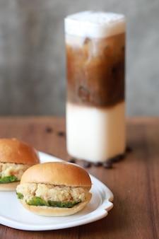 Hamburger wieprzowy i ser i kawa mrożona fastfood i śniadanie, które kładą na drewnianym stole w restauracji.