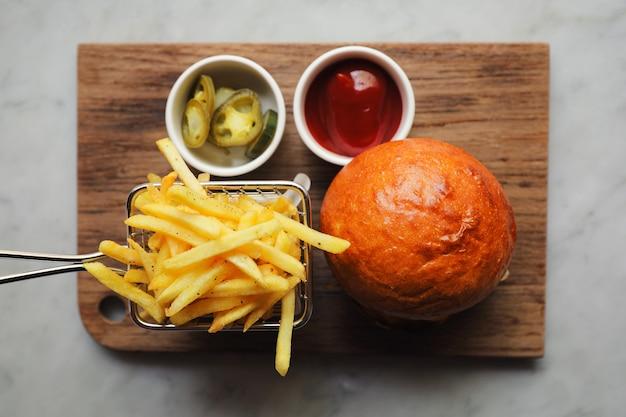 Hamburger wołowy z frytkami i ketchupem na barda z drewna