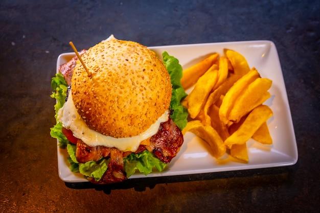 Hamburger z boczkiem i frytkami na czarnym tle, na białym talerzu