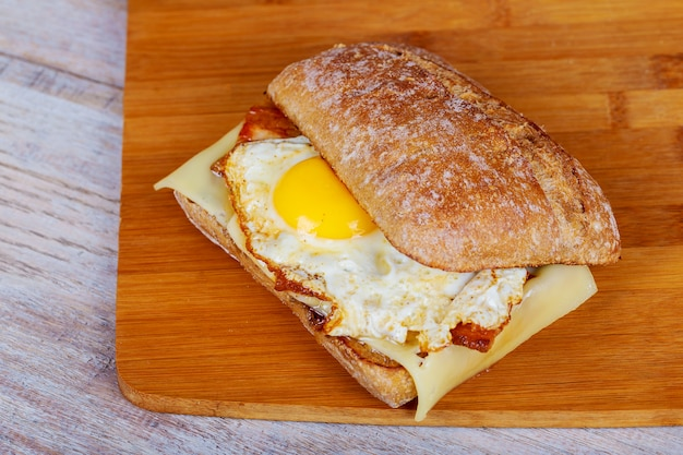Hamburger z boczkiem, jajkiem i frytkami na drewnianej desce do krojenia.