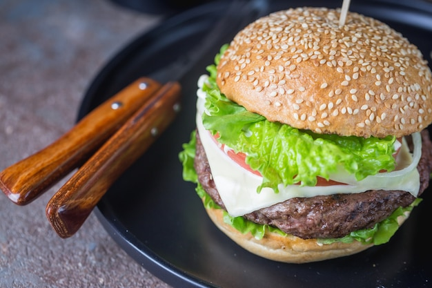 Hamburger z burgerem mięsnym wołowym i świeżymi warzywami na ciemnym tle. smaczne fast foody.