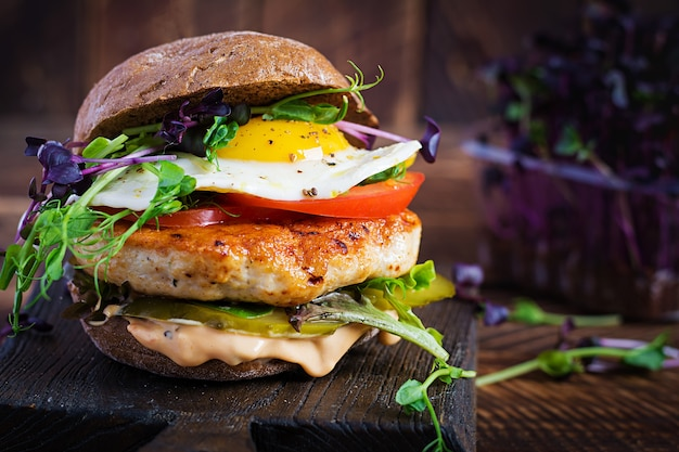 Hamburger z burgerem z kurczaka, pomidorami, ogórkiem kiszonym i jajkiem sadzonym