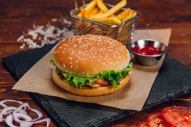 Hamburger z frytkami i keczupem na stole w restauracji