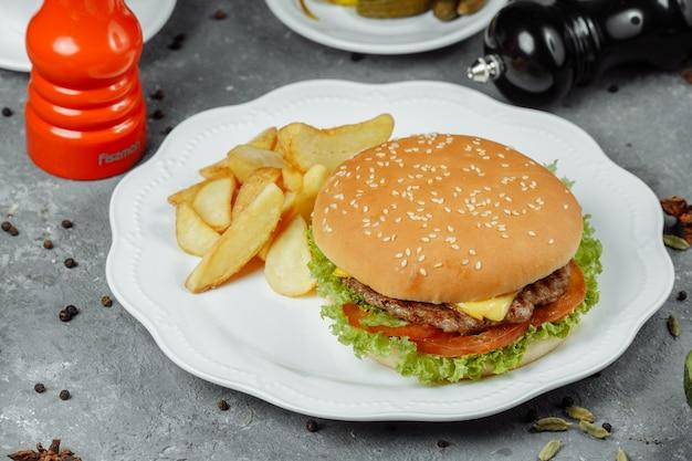 Hamburger z frytkami i surówką na talerzu.