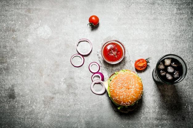 Hamburger z keczupem pomidorowym i sodą na kamiennym stole. widok z góry.