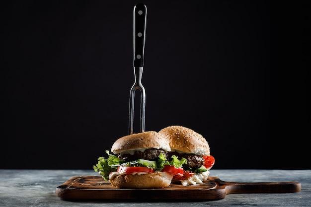 Hamburger z klopsikami na czarno. z zablokowanym widelcem.