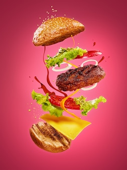 Hamburger z latającymi składnikami na tle róży. koncepcja reklamowa