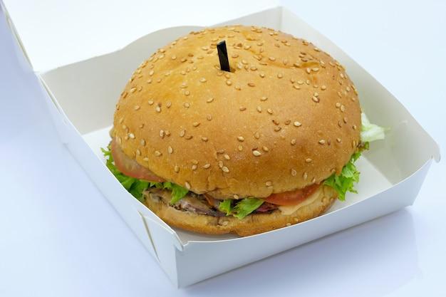 Hamburger z mięsem, sałatą i pomidorami w tekturowym pudełku.