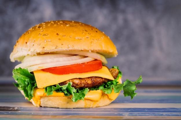 Hamburger z podwójnym mięsem, pomidorem, serem, cebulą.