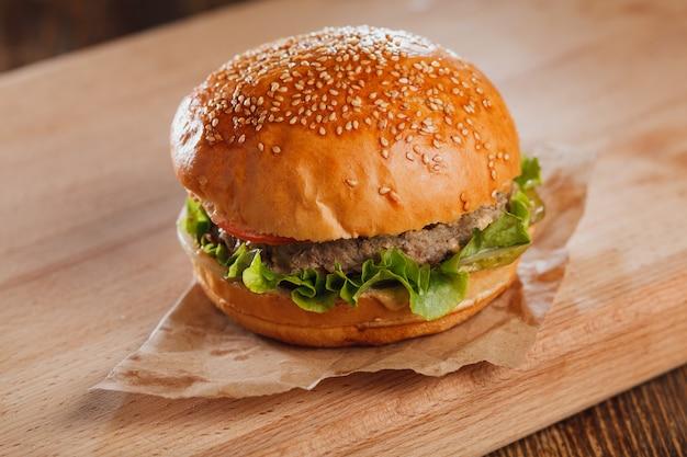 Hamburger z serem na drewnianym stole