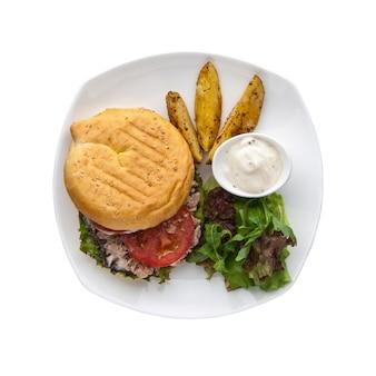 Hamburger z sosem i ziemniakami w talerzu na białym tle, widok z góry