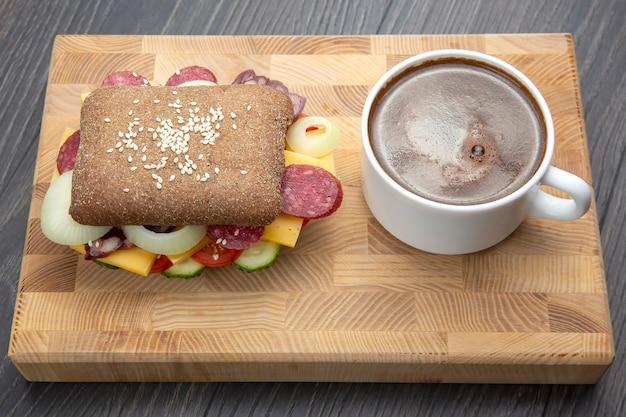 Hamburger z warzywami i kiełbasą oraz kawą. fast food i śniadanie. kalorie i dieta.