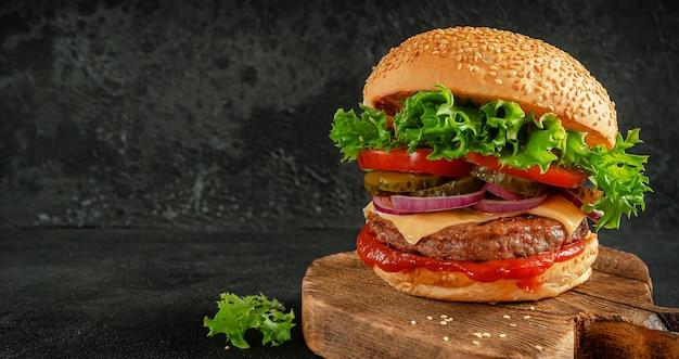 Hamburger z warzywami, keczupem, cheddarem i ogórkiem kiszonym na desce