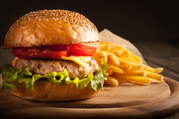 Hamburger z wołowiną, cebulą, pomidorem, sałatą i serem.