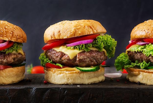 Hamburger z wołowiny mięsnym hamburgerem i świeżymi warzywami na ciemnym tle. smaczne jedzenie.