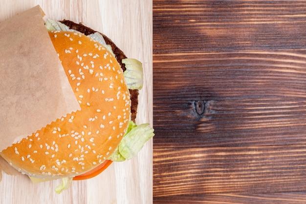 Hamburgeru odgórny widok od strony na drewnianym tle.