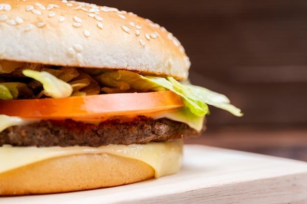 Hamburgeru zakończenie z stroną na drewnianym tle.
