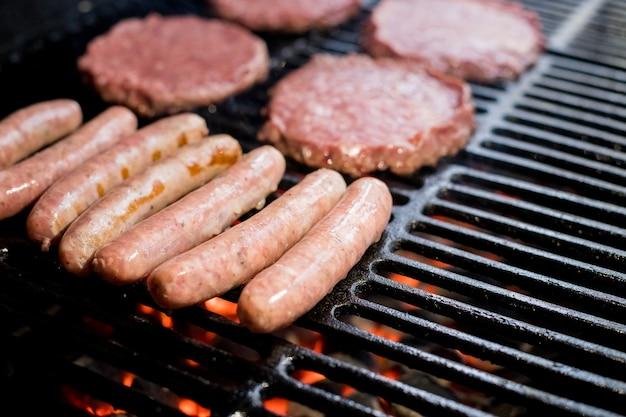 Hamburgery na grillu z tańczącymi płomieniami gotowane do perfekcji. zbliżenie niektórych świeżych i soczystych hamburgerów gotowanych na grillu. hamburgery wołowe gotowane
