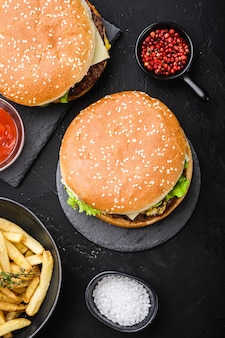 Hamburgery wołowe na czarnym tle z teksturą, widok z góry.
