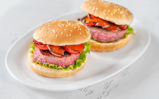 Hamburgery z grillowaną papryką na białym talerzu służącym