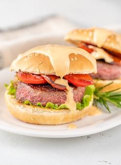 Hamburgery z grillowaną papryką polane pikantnym sosem na białym talerzu do serwowania
