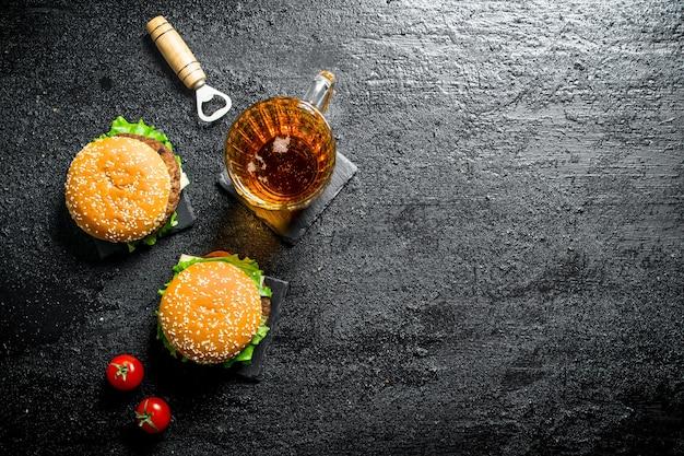 Hamburgery z piwem w szklance i pomidorami. na czarnym tle rustykalnym